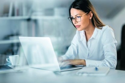 Young_beautiful_businesswoman_working_on_her_computer_in_the_office._The_view_is_through_glass.